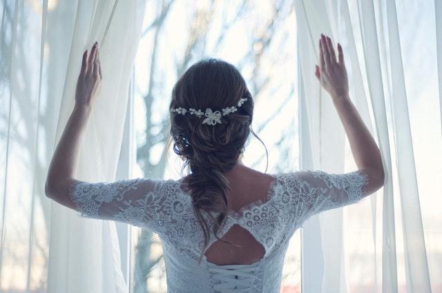 Nevěsta v bílých krajkových šatech stojící u okna