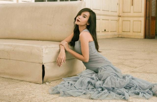 Dívka v kouřových tylových šatech sedící na podlaze